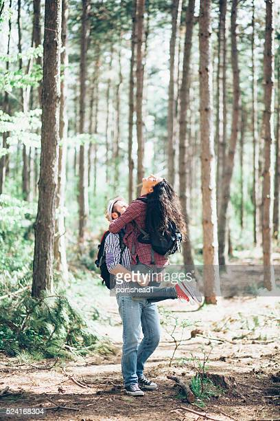 Man lifting his girlfriend at the forest