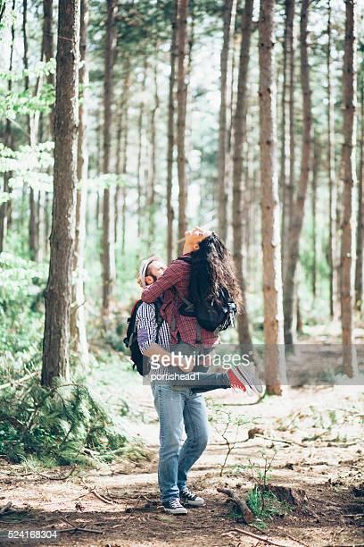 Homem levantando sua namorada na floresta