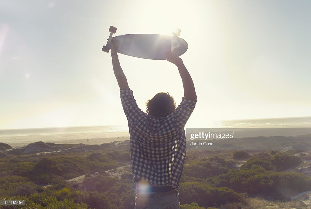 Portrait of a young man lifting his skateboard over his head while standing on a sunny peak observing a breathtaking beach landscape