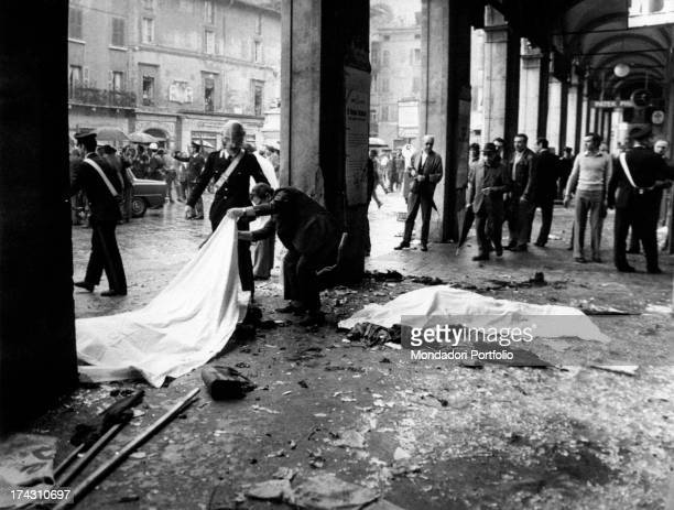A man lifting the sheet covering one of the victims of the massacre of Piazza della Loggia Brescia 28th May 1974