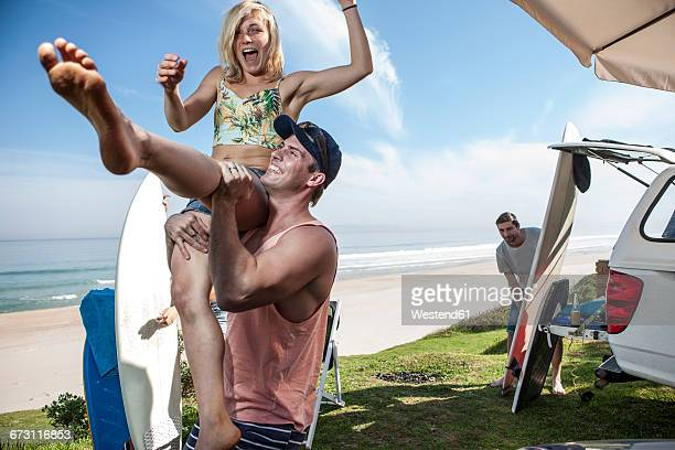 Man lifting up excited woman at the coast