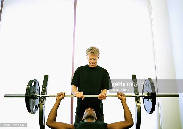 Man lifting weight with spotter