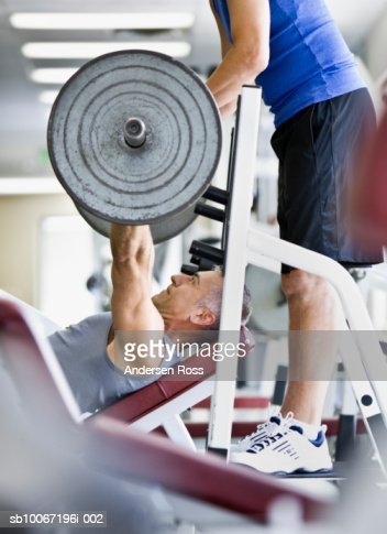Man lifting weights, friend assisting, side view : Stock Photo