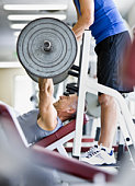 Man lifting weights, friend assisting, side view