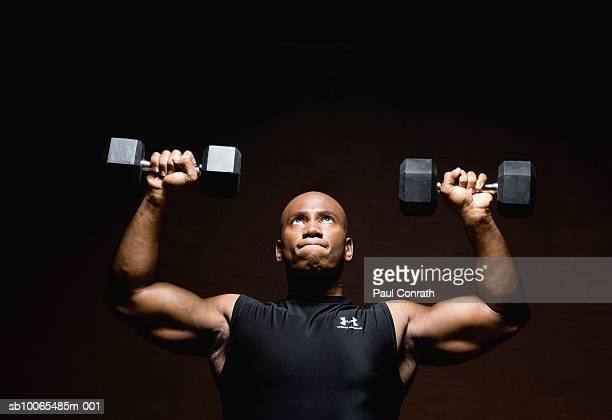Man lifting weights, looking up, studio shot