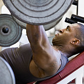 Man lifting weights on weight bench, profile