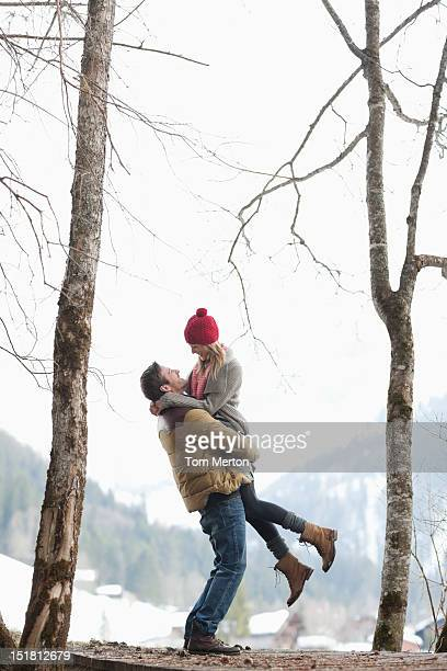 Man lifting woman in snowy woods