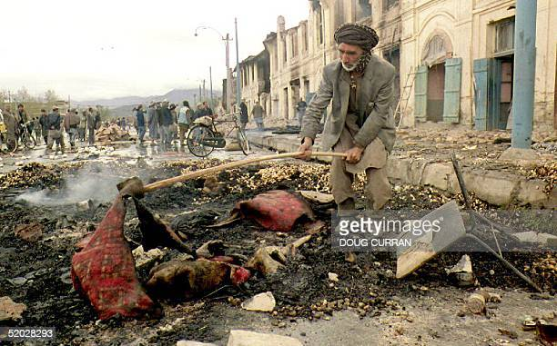 A man lifts burnt carpets out of the ashes 28 April 1992 in a street in the Afghan capital one day after fierce fighting between rival mujahedeen...