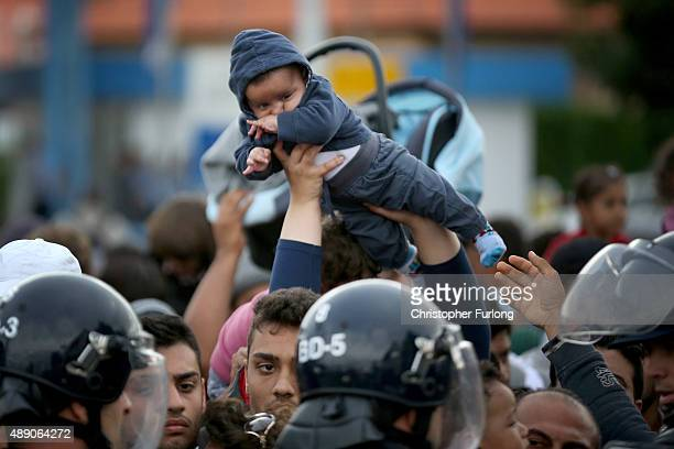 A man lifts his child above his head to avoid the crush as migrants are held back by Slovenian riot police in the small Croatian village of Harmica...
