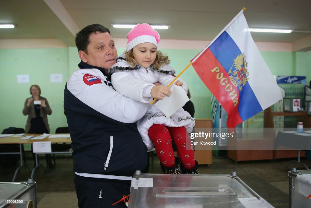 A man lifts his daughter holding a Russian flag to help cast his vote on March 16, 2014 in Bachchisaray, Ukraine. Crimeans go to the polls today in a vote that which will decide whether the peninsular should secede from mainland Ukraine. The referendum, which has been dismissed as illegal by the West, follows the ousting of President Viktor Yanukovych by pro-Western and nationalist protesters. As the standoff between pro-Russian forces and the Ukrainian military continues in the Crimean peninsula, world leaders are continuing to push for a diplomatic solution to the escalating situation.
