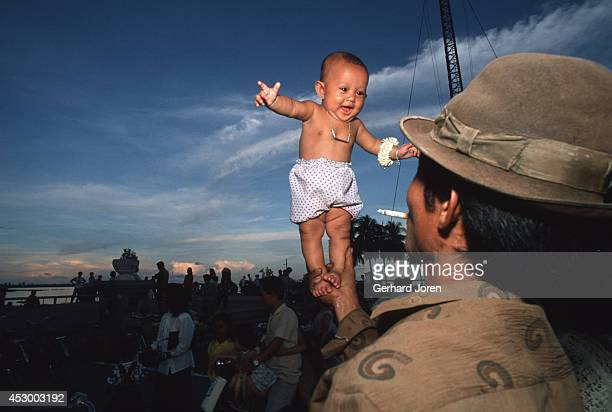 A man lifts his threemonthold daughter by the Tonle Sap River in Phnom Penh