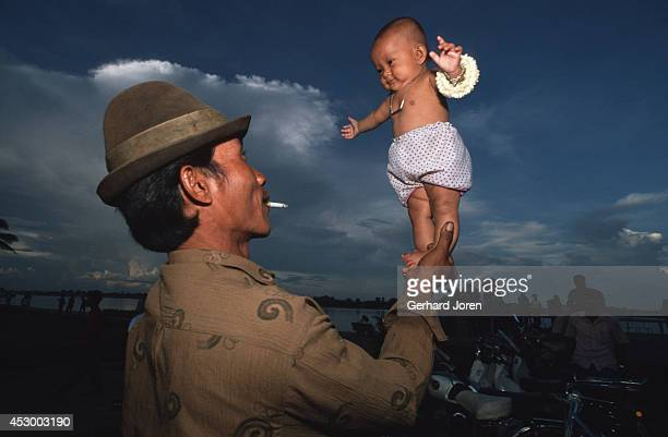 A man lifts his threemonthold daugther by the Tonle Sap River in Phnom Penh