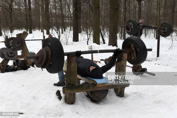 A man lifts weight in an outdoor selfmade gym in Timiryazevsky Park in Moscow on February 18 2017 / AFP PHOTO / VASILY MAXIMOV