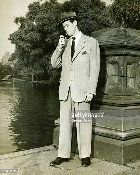 Mann, die Beleuchtung Zigarette von lake im park (B & W