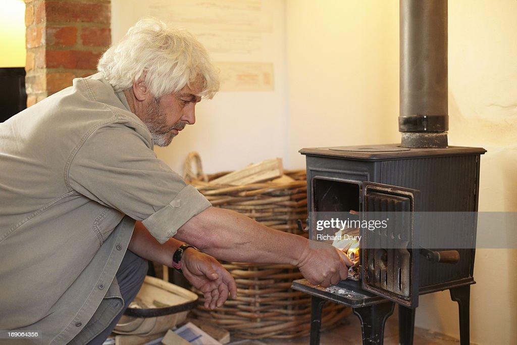 Man lighting fire in woodburner