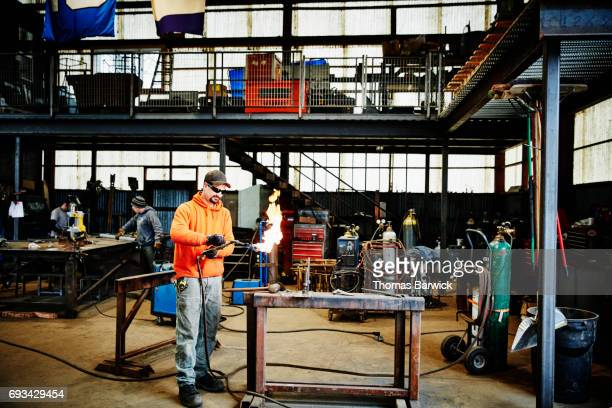 Man lighting torch in metal workshop before shaping metal for project