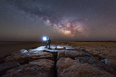 Midnight explorer walking a long a jetty under the night sky in New Jersey.