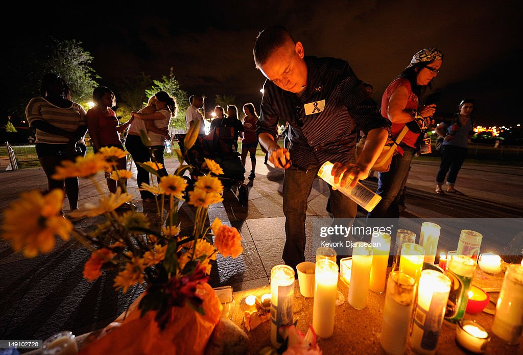 A man lights a candle as mourners gather at the fountain of Aurora Municipal Center after a prayer vigil for the 12 victims of Friday's mass shooting at the Century 16 movie theater, on July 22, 2012 in Aurora, Colorado. Suspect James Holmes, allegedly went on a shooting spree and killed 12 people and injured 59 during an early morning screening of 'The Dark Knight Rises.'