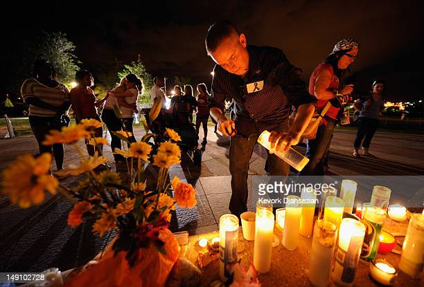 A man lights a candle as mourners gather at the fountain of Aurora Municipal Center after a prayer vigil for the 12 victims of Friday's mass shooting...