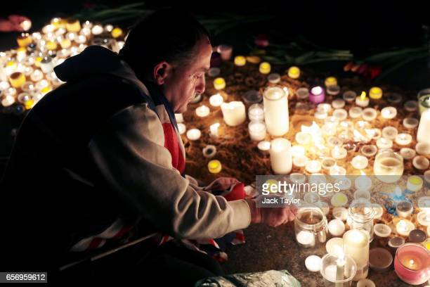 A man lights a candle during a candlelit vigil at Trafalgar Square on March 23 2017 in London England Four People were killed in Westminster London...