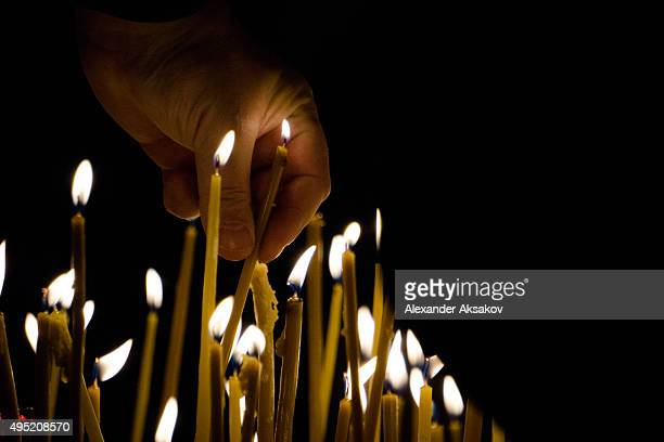 A man lights a candle during a requiem in memory of the victims of the plane crash in Kazan Cathedral on November 1 2015 in St Petersburg Russia...