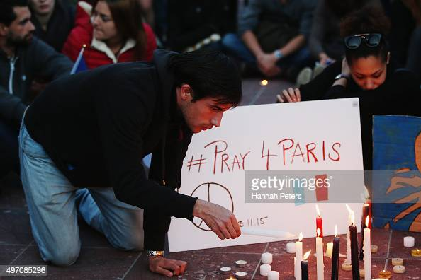 A man lights a candle during a vigil in Aotea Square to remember victims of the Paris attacks on November 14 2015 in Auckland New Zealand According...