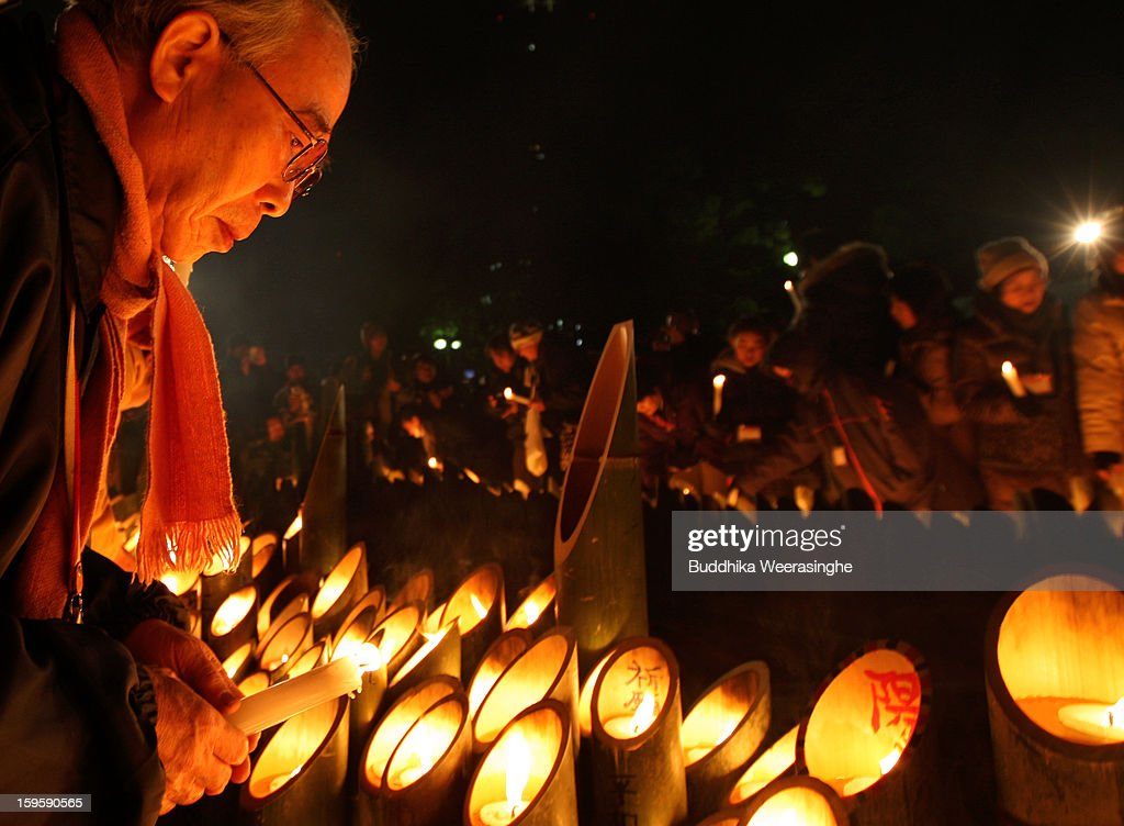 A man lights a candle for victims of the 1995 'Great Hanshin earthquake' during a memorial ceremony on January 17, 2013 in Kobe, Japan. Memorial services were held to mark the 18th anniversary of the 1995 massive earthquake, hundreds of people gathered early this morning to pay their respects and light bamboo lanterns in the park for more than 6,400 people who lost their lives in the 7.3 magnitude earthquake.