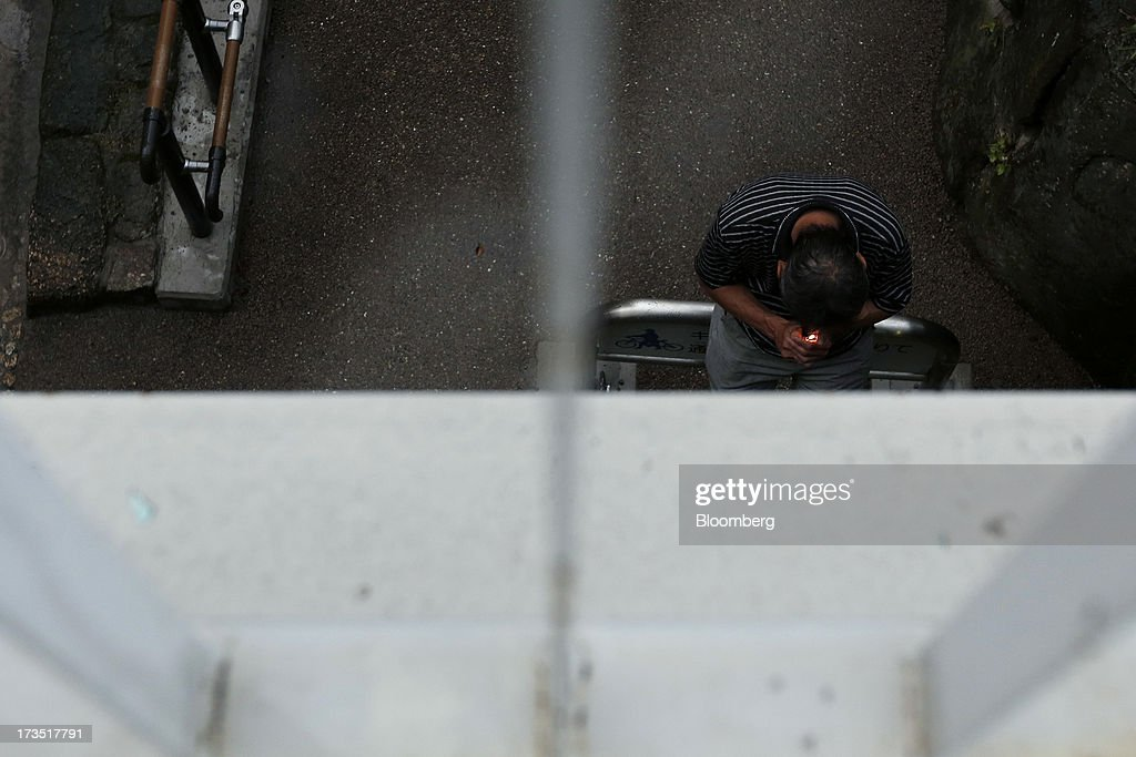 A man lights a cigarette under a bridge in Tokyo, Japan, on Monday, July 8, 2013. The number of Japanese seniors living alone will rise 54 percent to 7.17 million in 2030 from 4.66 million in 2010, according to the National Institute of Population and Social Security Research, set up by the Ministry of Health, Labour and Welfare. To manage the costs stemming from the aging society, the government aims to push back the pension age to 65 from 60 in stages through 2025. Photographer: Kiyoshi Ota/Bloomberg via Getty Images