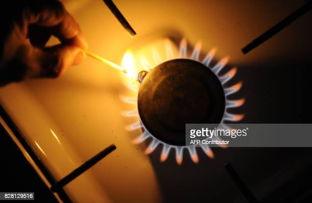 A man lights a match on the flame of a gas stove on January 6 2009 at a kitchen in Berlin Germany's economy minister called on Ukraine and Russia to...