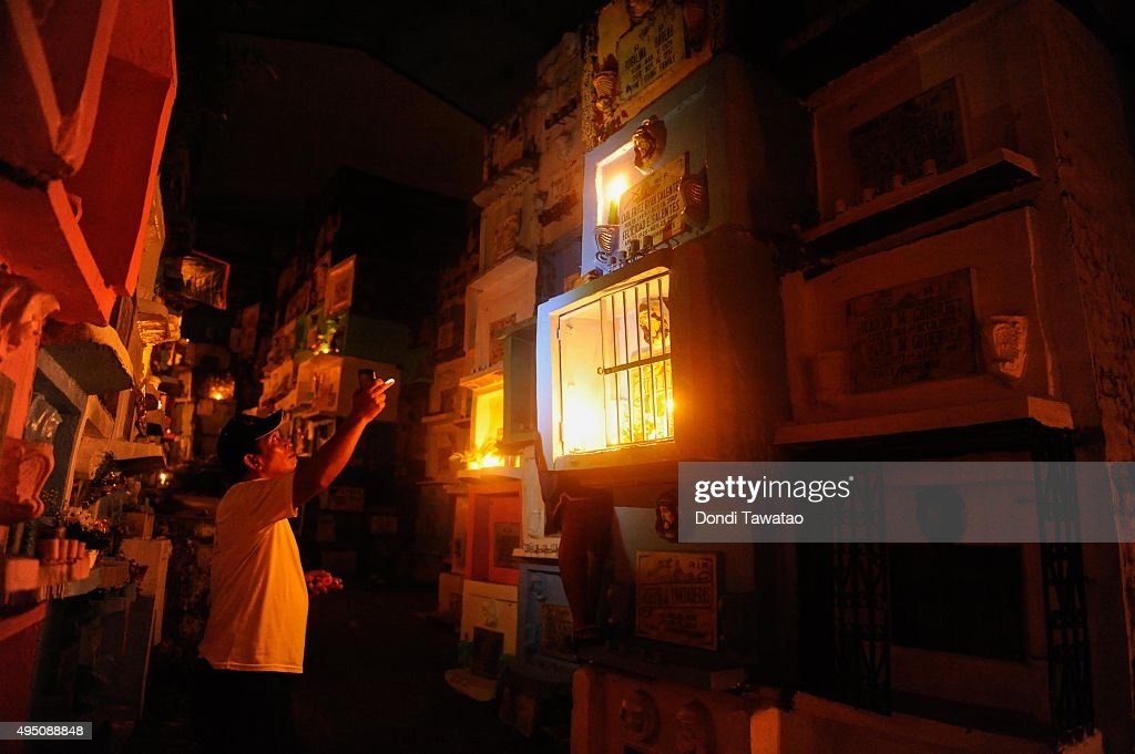 Man lights candles and pray at a public cemetery on october 31 2015