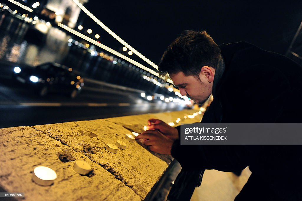 A man lights candles at the bank of Danube River in Budapest near the Chain Bridge, the oldest Hungarian bridge on February 25, 2013 during a memorial day for victims of communist dictatorships. AFP PHOTO / ATTILA KISBENEDEK
