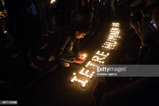 A man lights candles in tribute to the victims of the attacks in and around Paris at the Place de la Republique square in Paris on November 14 2015...