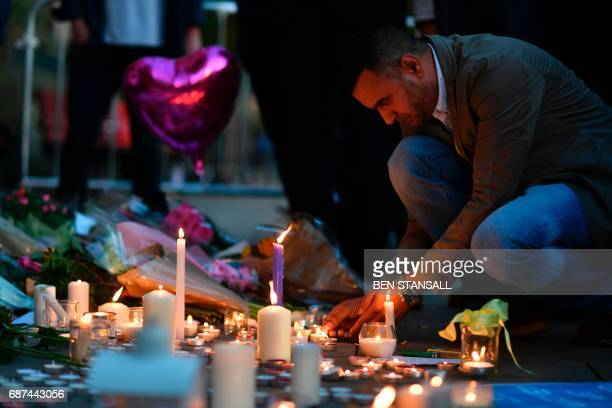 A man lights candles set up in front of floral tributes in Albert Square in Manchester northwest England on May 23 in solidarity with those killed...