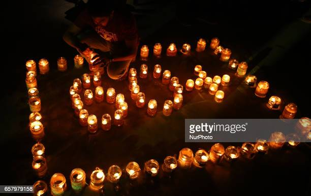 A man lights lamps to form the number 60 representing the 60 minutes of Earth Hour during Earth Hour in Colombo Sri Lanka on March 25 2017