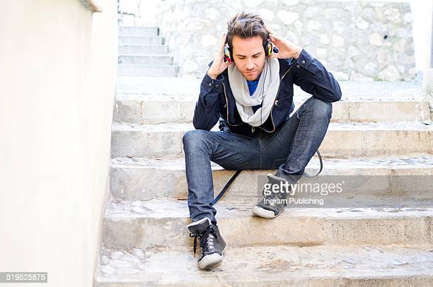 Man listening music through headphones while sitting on steps