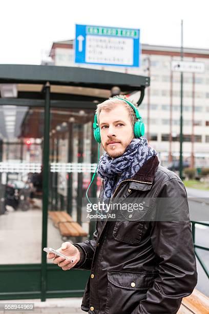 Man listening music through mobile phone while waiting at bus stop