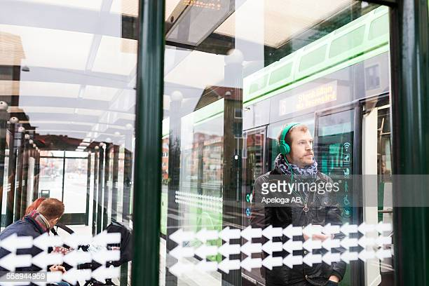 Man listening music while couple sitting at bus stop