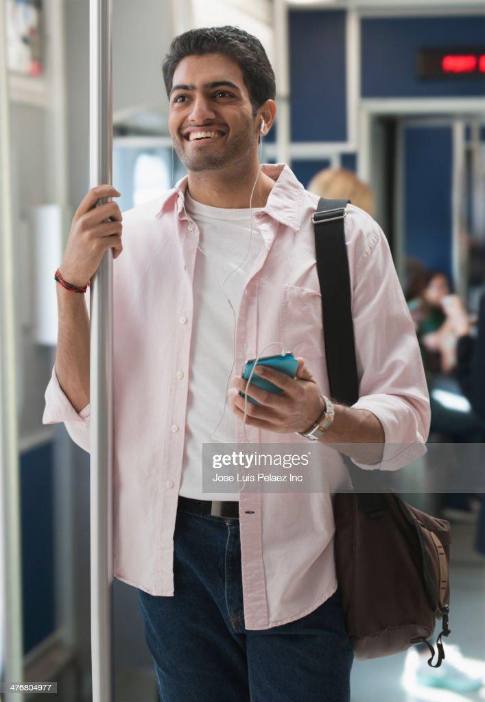 Man listening to earphones on subway train