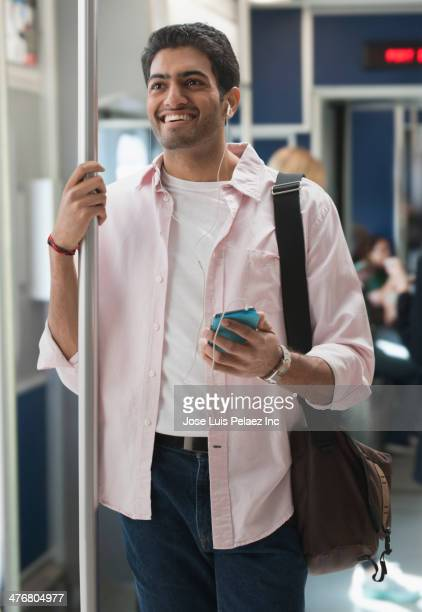 Man listening to earphones on subway train