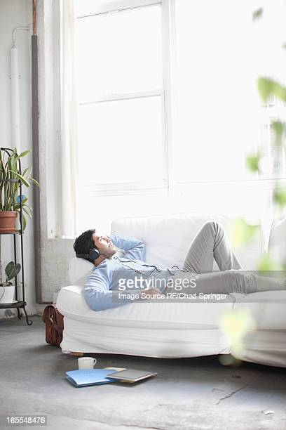 Man listening to headphones on sofa