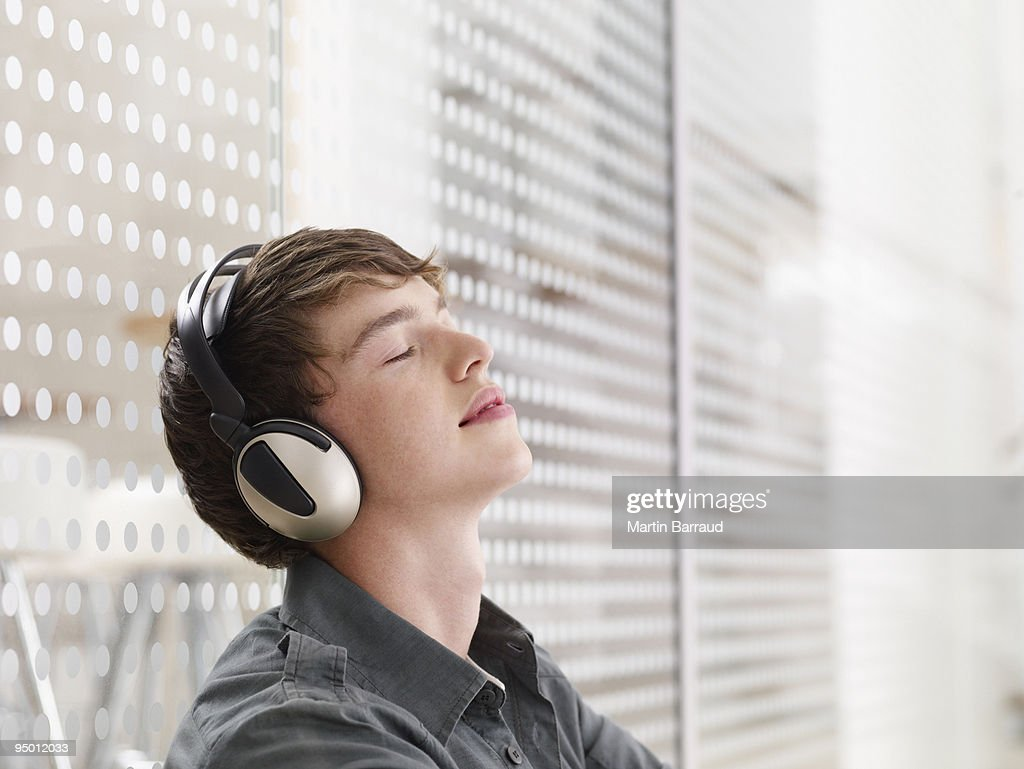 Man listening to headphones with eyes closed : Stock Photo
