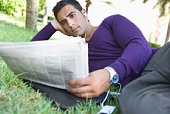 Man listening to MP3 player and reading newspaper outdoors