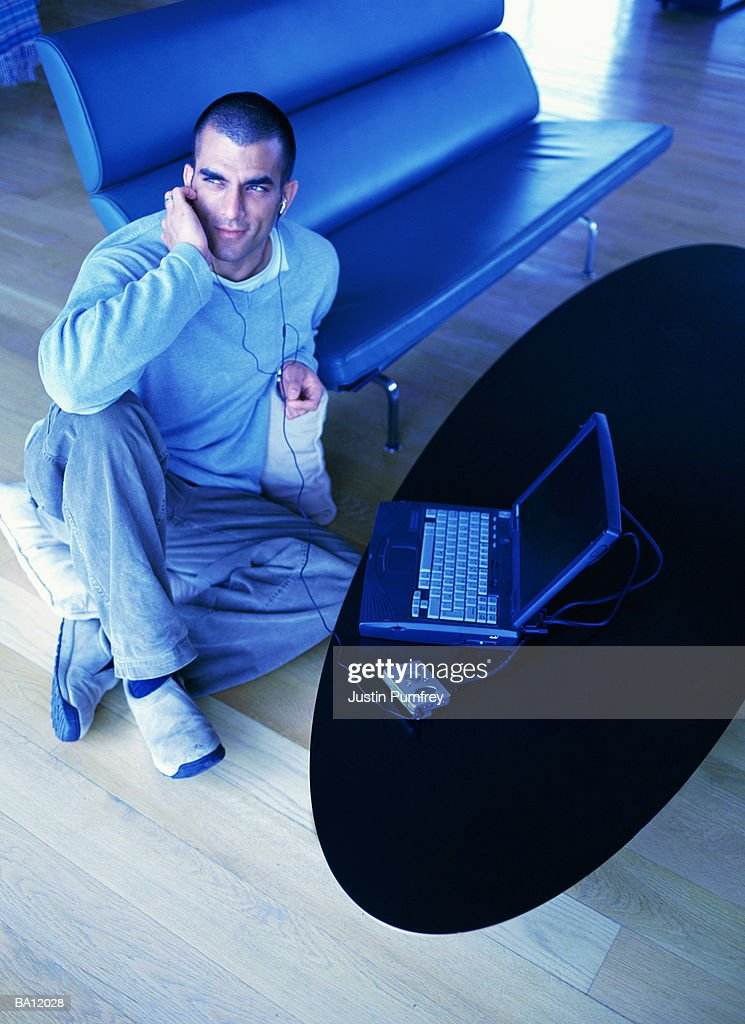 Man listening to MP3 player, laptop on table beside : Stock Photo