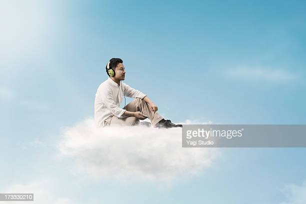 Man listening to music above the clouds