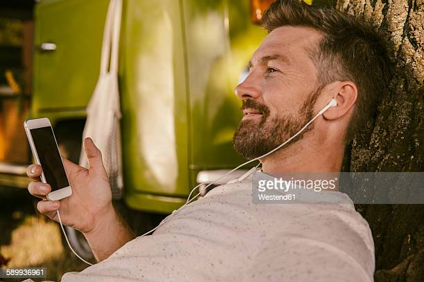 Man listening to music at tree in front of van
