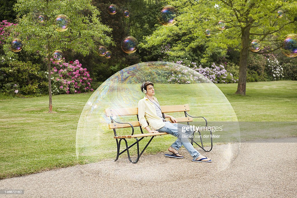 man listening to music sitting in bubble. : Stock Photo