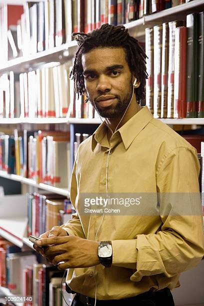 Man listening to music with headphones in library