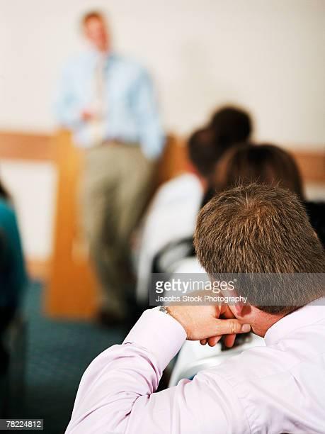 Man listening to speaker at presentation