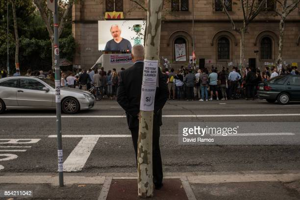 A man listens to Julian Assange holding a video conference with Catalan students outside the University of Barcelona on September 26 2017 in...