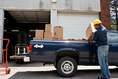 Man loading boxes into truck bed